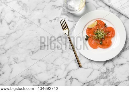 Salmon Carpaccio With Capers, Microgreens And Lemon Served On White Marble Table, Flat Lay. Space Fo