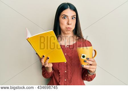 Young hispanic woman reading book drinking cup of tea puffing cheeks with funny face. mouth inflated with air, catching air.