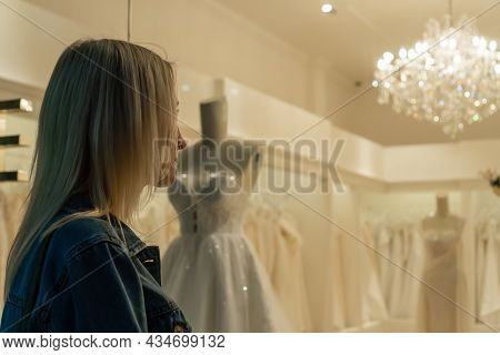 Young Blonde Woman Stands At The Window Of A Wedding Shop And Looks At Wedding Dresses. Concept Of A