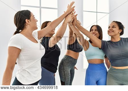 Group of young hispanic sporty women smiling happy high five with hands raised up at sport center.