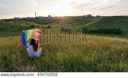 Bisexual, Lesbian, Woman, Transgender Sitting On The Grass And Field And Holds Lgbt Flag On The Gree