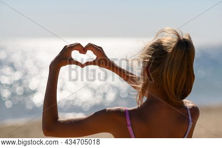 A Girl On The Beach Holds Her Hands In The Shape Of A Heart Against The Background Of Sun Glare From