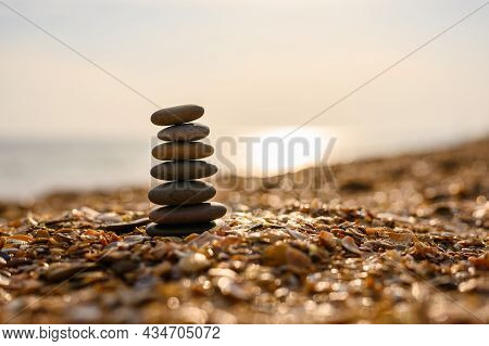 Black Pebble Pyramid On A Seashell Beach At Sunset. Calm Scene And Privacy. Selective Focus, Narrow