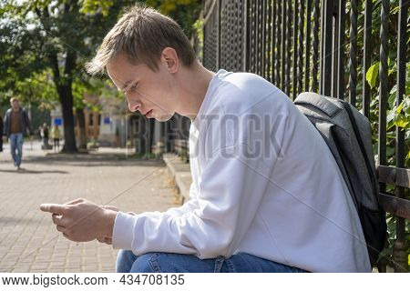A Young Guy Of 20-25 Years Old With A Backpack Sits At The Metal Fence Of The Park And Looks At The