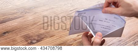 Paycheck In Open Envelope. Holding Payroll Cheque