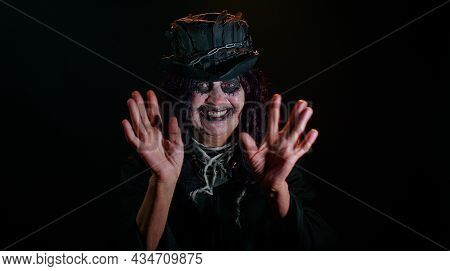 Frightening Senior Woman With Halloween Witch Makeup Waves Hand Palm In Hello Gesture Welcomes Someo
