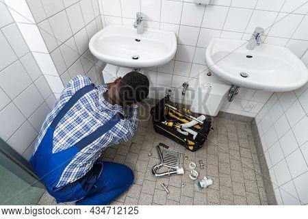 Plumber Fixing Pipe In Bathroom. Plumbing Maintenance In Bathroom