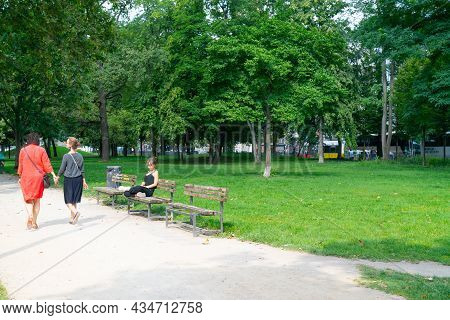 Berlin, Germany - August  27 2017; Woman Sits Crossed Legged Reading In Exercise Clothing On Park Be