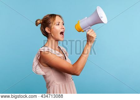 Strict Blonde Young Adult Woman With Hair Buns In Summer Dress Loudly Screaming At Megaphone, Making