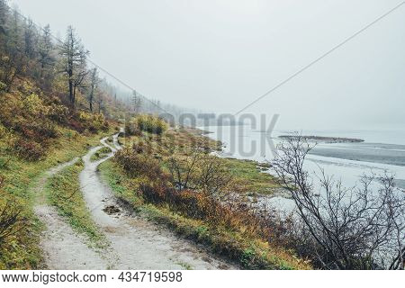 Scenic Autumn Landscape With Motley Plants And Footpath Along Mountain Lake In Dense Fog. Atmospheri