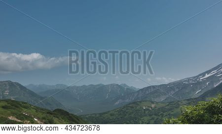 The Mountains Are Covered With Green Vegetation. The Ridge Extends To The Horizon. A River Meanders