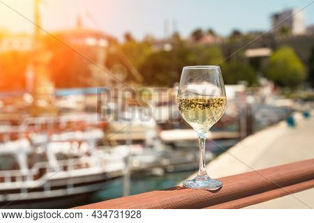 Glass Of White Wine Against The Backdrop Of The Mediterranean Sea And The Port With Yachts In A Tour