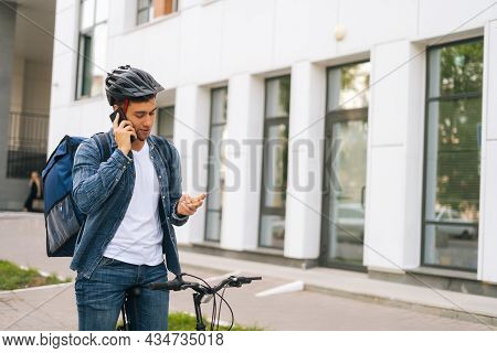 Medium Shot Of Bicycle Courier Male With Thermal Backpack Talking On Mobile Phone To Customer, Looki