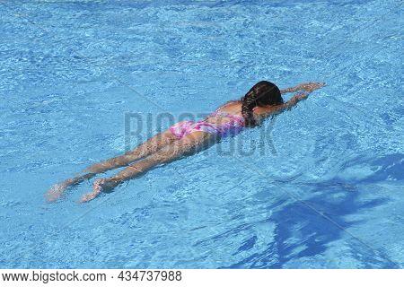 Little Girl At Swimming Pool. Girl Having Fun Swimming Pool On Summer Vacation. Swimming Girl.