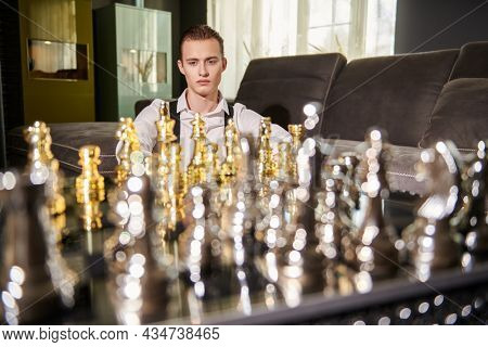 Strategic decision in business. Well-groomed smart man in elegant clothes playing chess in a modern luxury interior.