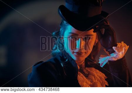 An elegant lady in a 19th century suit against a dark background in mixed color light. Historical hairstyle and makeup.