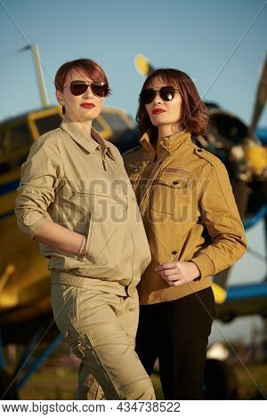 Two beautiful professional female commercial aviation pilots in uniform and sunglasses stand in front of their plane at the airfield. Aviation.