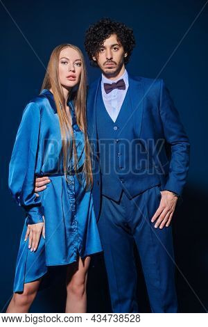 A pair of young handsome man and woman in elegant evening wear on a dark blue background. Beauty, fashion portrait.