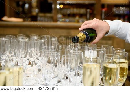 Closeup Of Serving Champagne From The Bottle In A Group Of Champagne Flutes Against A Colourfull Bac