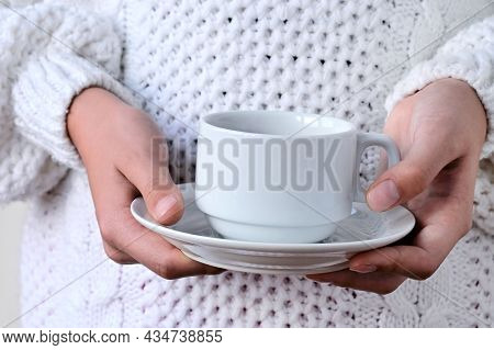 Close-up Of Girl's Hands In Warm Knitted White Sweater Holding White Cup And Saucer. Concept Of Wint