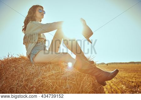 A beautiful stylish hippie girl in western style clothes sits on a haystack in the background of the setting sun looking into the distance. Wild west and hippie style. Copy space.