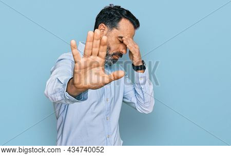 Middle aged man with beard wearing business shirt covering eyes with hands and doing stop gesture with sad and fear expression. embarrassed and negative concept.