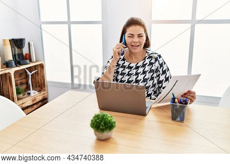 Middle age hispanic woman working at the office with laptop speaking on the phone winking looking at the camera with sexy expression, cheerful and happy face.