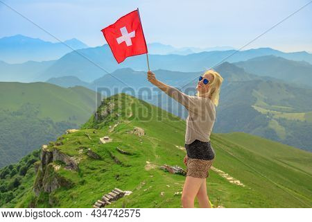 Tourist Woman With Swiss Flag On Monte Generoso Calvagione Top. Skyline View Of Lugano Lake Of Ticin