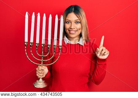 Beautiful hispanic woman holding menorah hanukkah jewish candle smiling with an idea or question pointing finger with happy face, number one