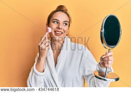 Young blonde woman wearing robe holding makeup remover brush winking looking at the camera with sexy expression, cheerful and happy face.
