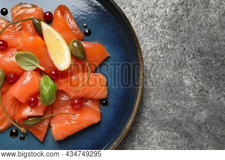 Salmon Carpaccio With Capers, Cranberries, Basil And Lemon On Grey Table, Top View