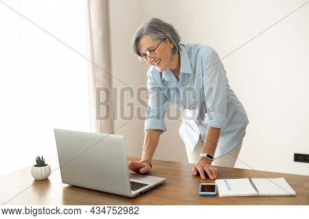 Senior Middle-aged Businesswoman Wearing Glasses, Looking At The Laptop Screen, Waiting To Get Conne