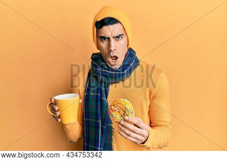 Handsome hispanic man eating doughnut and drinking coffee in shock face, looking skeptical and sarcastic, surprised with open mouth