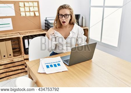 Young caucasian woman working at the office wearing glasses scared and amazed with open mouth for surprise, disbelief face
