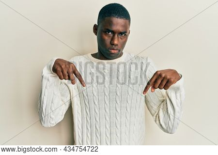 Young african american man wearing casual clothes pointing down looking sad and upset, indicating direction with fingers, unhappy and depressed.