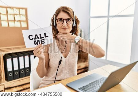 Middle age brunette woman wearing operator headset holding call me banner cutting throat with hand as knife, threaten aggression with furious violence