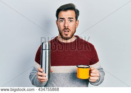 Handsome caucasian man with beard drinking a cup of coffee holding thermo in shock face, looking skeptical and sarcastic, surprised with open mouth