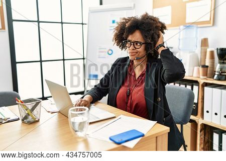 African american woman with afro hair working at the office wearing operator headset confuse and wondering about question. uncertain with doubt, thinking with hand on head. pensive concept.