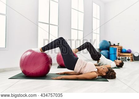 Young african american woman and hispanic man exercising at pilates room, stretching body and doing yoga pose, training strength and balance