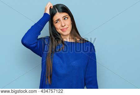 Young hispanic woman wearing casual clothes confuse and wonder about question. uncertain with doubt, thinking with hand on head. pensive concept.