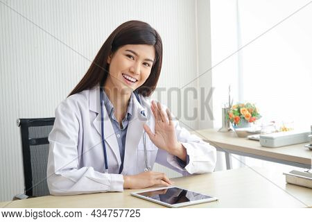 Asian Female Doctor Sitting In Office Smile Happily, Raise Your Hand To Say Hello. Hospital Medical