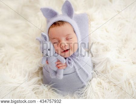 Little beautiful newborn baby girl swaadled in fabric and wearing hat with bunny ears sleeping on fur and smiling during studio photoshoot. Cute infant child kid napping holdint toy in tiny hands