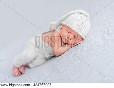 Newborn baby boy wearing knitted pants and hat sleeping and holding tiny hands under his cheeks. Adorable infant child napping in studio