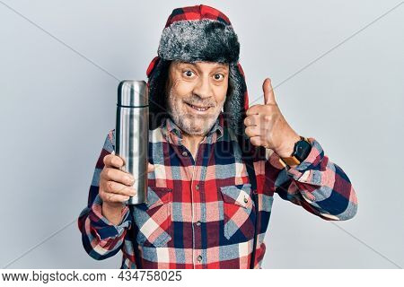 Handsome mature handyman wearing winter hat with ear flaps holding thermo smiling happy and positive, thumb up doing excellent and approval sign
