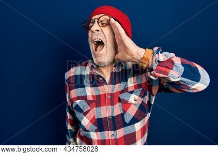 Handsome mature man wearing hipster look with wool cap shouting and screaming loud to side with hand on mouth. communication concept.