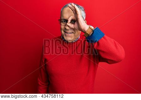 Handsome senior man with grey hair wearing casual clothes and glasses doing ok gesture with hand smiling, eye looking through fingers with happy face.