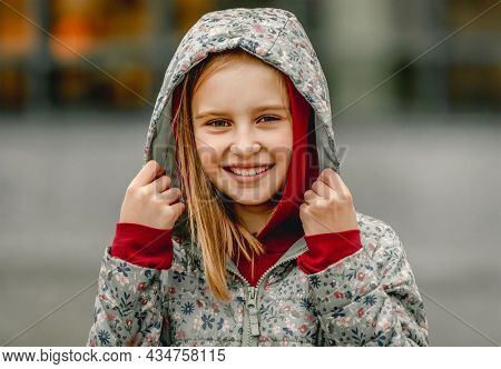 Preteen girl wearing hood and smiling at the street at autumn. Pretty female kid portrait outdoors in fall season