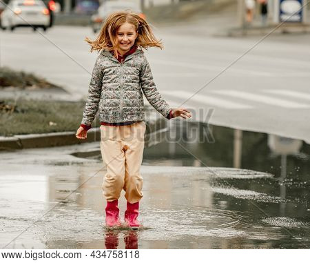 Preteen girl wearing rubber boots jumping through puddles at autumn at street. Pretty female kid in gumboots in rainy day outdoors