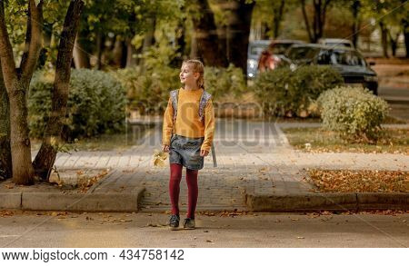 Preteen school girl with backpack holding yellow leaves in her hand and walking. Pretty pupil female kid after education class in autumn park