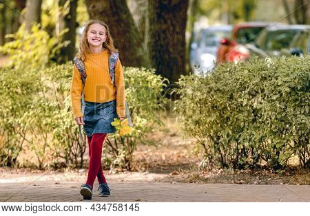 Preteen school girl with backpack holding yellow leaves in her hand, looking at camera and smiling. Pretty pupil female kid after class in autumn park